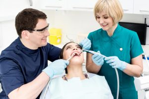 Dentist and hygenist performing dental services